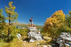 Pai e crianças que exploram a floresta de pedra, formação de rocha natural, criada pelas camadas múltiplas de pedra, situadas per fotos de stock