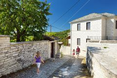 Pai e crianças que exploram a vila de Monodendri com suas construções pedra-feitas tradicionais e passagens de pedra, área de Zag imagens de stock