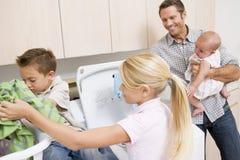 Pai e crianças que fazem a lavanderia Imagem de Stock
