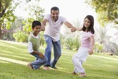 Pai e crianças que jogam o parque foto de stock