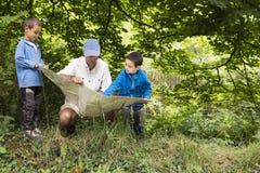 Pai e crianças que leem o mapa na natureza Fotografia de Stock Royalty Free