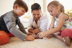 Pai e crianças que passam o tempo que usa junto a tabuleta digital imagem de stock royalty free