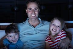 Pai e crianças que prestam atenção ao programa no Tog da tevê Fotos de Stock