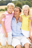 Pai e crianças que sentam-se em balas da palha em Harv Imagens de Stock Royalty Free