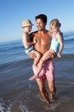 Pai e crianças que têm o divertimento na praia Imagens de Stock Royalty Free
