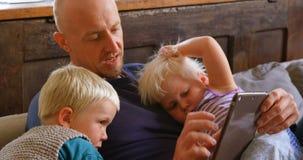 Pai e crianças que usam a tabuleta digital 4k vídeos de arquivo