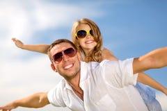 Pai e criança felizes nos óculos de sol sobre o céu azul Fotos de Stock Royalty Free