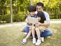 Pai e crianças asiáticos que usam a tabuleta fora Fotografia de Stock Royalty Free