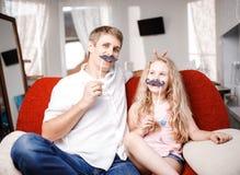 Pai e filha alegres com bigode artificial ao sentar o togheter na cadeira vermelha em casa Fotos de Stock Royalty Free