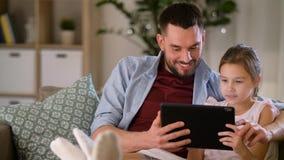 Pai e filha com PC da tabuleta em casa vídeos de arquivo