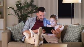 Pai e filha com PC da tabuleta em casa video estoque