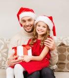 Pai e filha de sorriso que guardam a caixa de presente fotos de stock