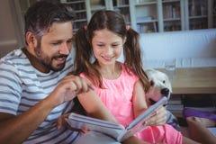 Pai e filha de sorriso que olham o álbum de fotografias na sala de visitas imagem de stock royalty free