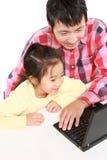 Pai e filha japoneses no laptop Fotografia de Stock Royalty Free