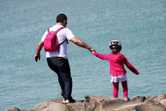 Pai e filha nas rochas para o mar Foto de Stock Royalty Free