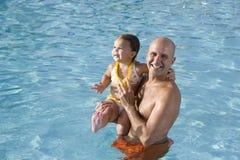Pai e filha nova que apreciam a piscina Imagem de Stock Royalty Free