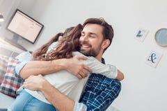 Pai e filha pequena em casa que sentam o homem que abraça a menina feliz fotos de stock