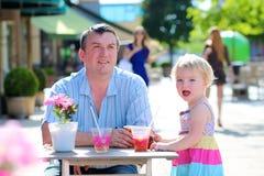 Pai e filha pequena que bebem no café Fotografia de Stock Royalty Free