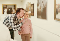 Pai e filha positivos em relação às pinturas no museu fotografia de stock royalty free