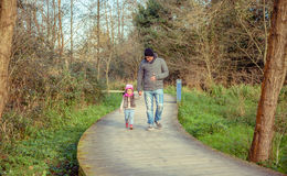 Pai e filha que andam unidas mantendo as mãos Imagens de Stock