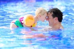 Pai e filha que apreciam a piscina Imagens de Stock Royalty Free