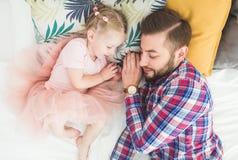 Pai e filha que dormem junto na cama fotografia de stock