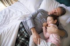 Pai e filha que dormem junto na cama no quarto fotografia de stock