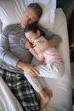 Pai e filha que dormem junto na cama no quarto fotografia de stock royalty free