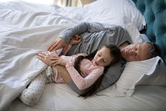 Pai e filha que dormem junto na cama no quarto imagem de stock