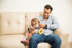 Pai e filha que escutam a música Imagens de Stock