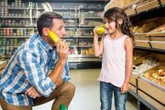 Pai e filha que jogam com bananas foto de stock royalty free
