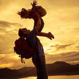 Pai e filha que jogam na costa do lago no por do sol t Foto de Stock