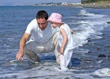 Pai e filha que jogam no mar Fotografia de Stock Royalty Free