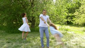 Pai e filha que jogam no parque, paizinho que gira sua dança da mãe da menina vídeos de arquivo