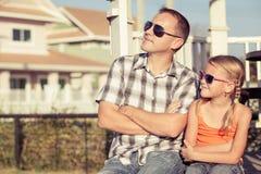Pai e filha que jogam perto da casa no tempo do dia Foto de Stock