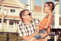Pai e filha que jogam perto da casa no tempo do dia Fotos de Stock