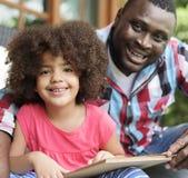 Pai e filha que lêem um livro foto de stock