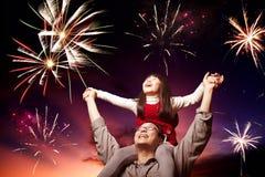 Pai e filha que olham fogos-de-artifício Fotografia de Stock