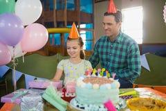 Pai e filha que olham presentes na tabela Fotografia de Stock Royalty Free