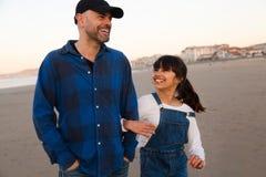 Pai e filha que riem ao andar na praia imagem de stock royalty free