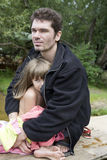 Pai e filha que sentam-se no banco do rio Fotografia de Stock