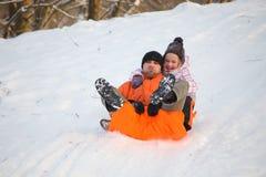 Pai e filha que têm o divertimento na neve Foto de Stock Royalty Free