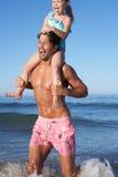 Pai e filha que têm o divertimento na praia Imagem de Stock Royalty Free