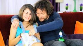 Pai e filha que têm o divertimento que joga com alimento video estoque