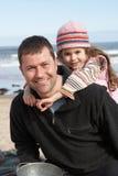 Pai e filha que têm o divertimento na praia junto Imagens de Stock