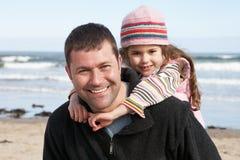 Pai e filha que têm o divertimento na praia junto Imagens de Stock Royalty Free
