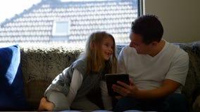 Pai e filha que usa a tabuleta digital na sala de visitas vídeos de arquivo