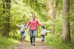 Pai e filhas que andam nas mãos da terra arrendada do trajeto Fotos de Stock