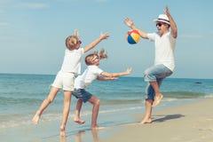 Pai e filhas que jogam na praia no tempo do por do sol Imagens de Stock