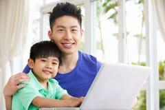 Pai e filho chineses que usa o portátil em casa fotos de stock royalty free